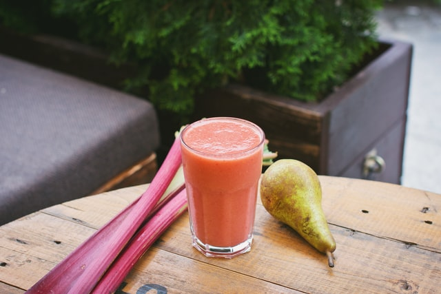 a wooden table with pear and rhubarb, and a glass filled with smoothie